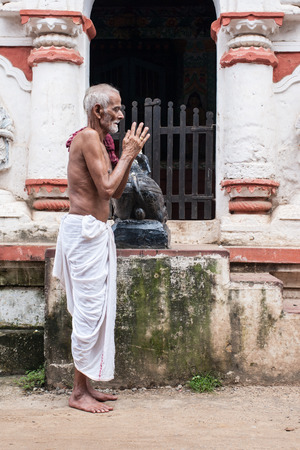 dhoti: PURI, INDIA, OCTOBER 9th 2010 - An old man praying outside a temple of Shiva in East India. Editorial