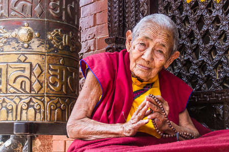 BOUDANATH, NEPAL - MAY 3 2013: An old Buddhist nun sitting outside a shrine in Boudanath, Nepal.