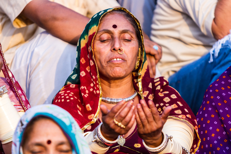 hindues: RISHIKESH, INDIA - MAY 15th 2013 A Hindu lady sits in meditation during a ceremony on the banks of the Ganges.