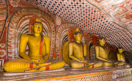 Statues of Buddha sitting in the ancient Dambulla Cave Temple in Sri Lanka.