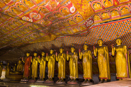 Statues of Buddha standing in the ancient Buddhist cave temple at Dambulla, Sri Lanka.