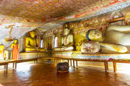 buddha sri lanka: Statues of Buddha sitting and reclining in the ancient Buddhist cave temple at Dambulla, Sri Lanka.