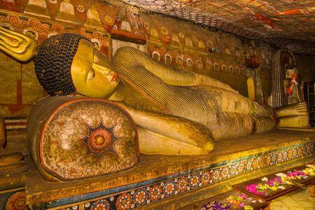 A statue of reclining Buddha in the ancient Buddhist cave temple at Dambulla, Sri Lanka.