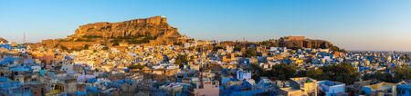 The blue city of Jodhpur with Mehrangarh Fort in the background at sunset.
