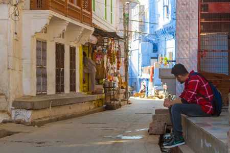 Jodhpur, India, 17th January 2017 -  A  young man sits in a quiet street in Jodhpur, India.