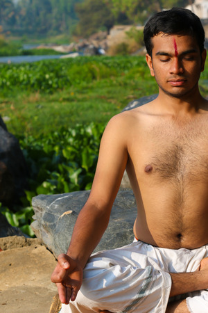 Indian man practicing yoga meditation next to a river  in South India.