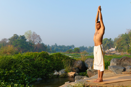 Indian man practicing yoga next to a river  in South India.