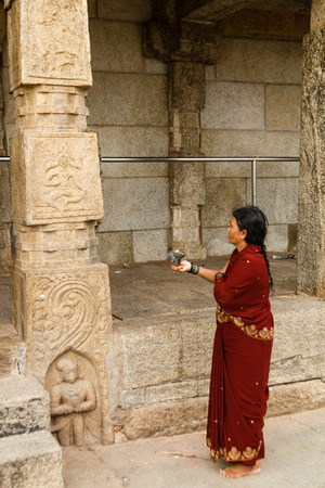 Nanjangud, India, 4th July 2017 -A woman worshipping a god carved on a temple pillar at Nanjangud in South India. Editorial