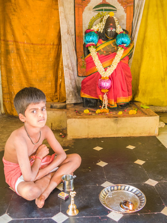 NANJANGUD, INDIA - FEB 1st 2008 - A brahmin boy at a shrine outside the temple of Nanjangud, South India.