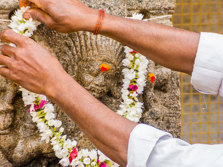 A Hindu offers a garland to a god carved on a stone pillar at the the temple of Shiva in Nanjangud, South India.
