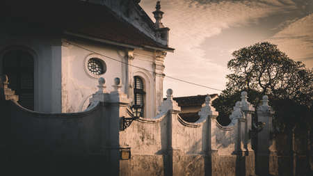 Old colonial church building and outside white walls with a street lamp in focus as evening light brighten up the wall.