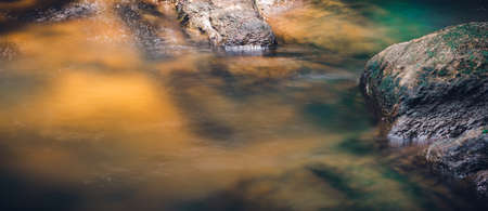 Small water stream and rocks in Bambarawana, light passing through the water and hits the green mossy bottom and glow, long exposure water flowing photograph,
