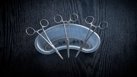 Hemostatic Forceps scissors lay flat on top of plastic equipment holder on a wooden table top, overhead view photograph.