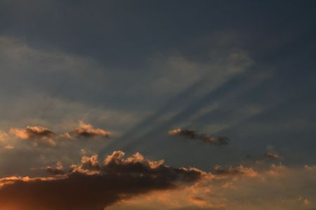 a bright and cloudy sunset or sunrise with sunrays filtered photo