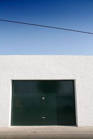 green door garage, white wall and blue sky, sidewalk and street photo