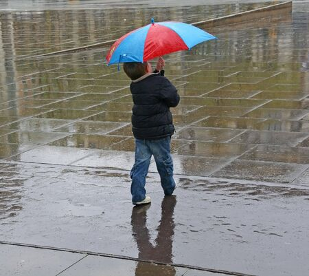 a kid alone with an umbrella in a rainy day