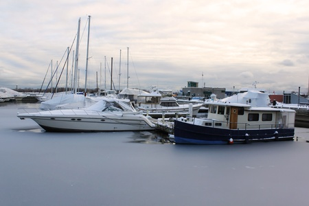 Frozen marina in winter with covered boats on ice - Toronto, Ontario, Canada photo