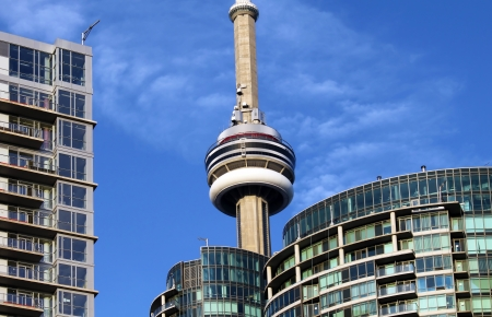 CN Tower and residential buildings against blue sky, Toronto, Ontario, Canada