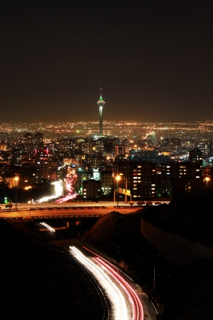 Tehran skyline illuminated at night with motion blur of cars photo