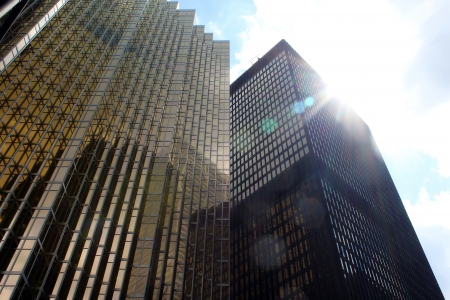 Office buildings in downtown Toronto against blue sky with clouds and sun 스톡 콘텐츠