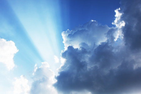 Dramatic blue sky with sun rays bursting through the clouds photo