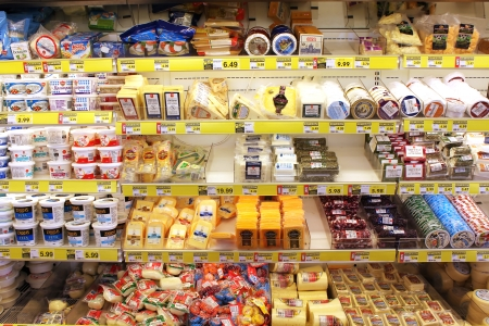 Variety of cheeses on shelves in a grocery store
