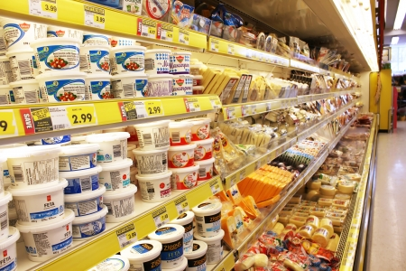Different brands of cheese on shelves in a grocery store 에디토리얼