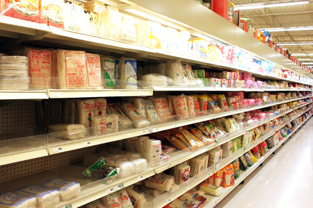 Different brands of noodles and snacks on the shelves in an Asian supermarket