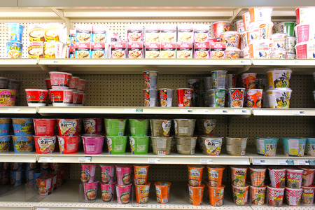 Variety of instant noodles with different flavors on the shelves of an Asian supermarket