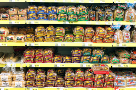 Variety of bread on shelves in a grocery store 報道画像