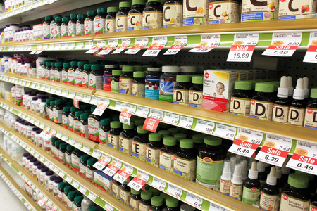 Different types of vitamins and supplements on shelves in a pharmacy