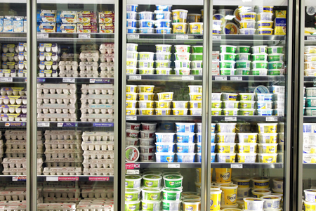 Eggs and dairy products on shelves in the fridge in a supermarket