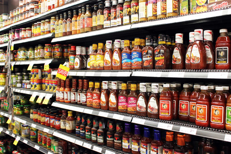 Variety of sauces and tomato ketchup bottles on shelves in a supermarket
