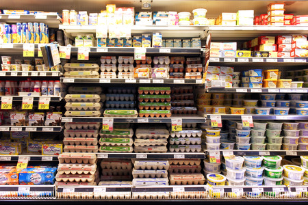 refrigerator with food: Eggs and dairy products on shelves in a supermarket