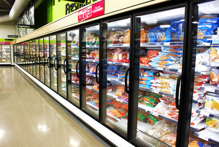 refrigerator with food: Frozen foods aisle in a supermarket