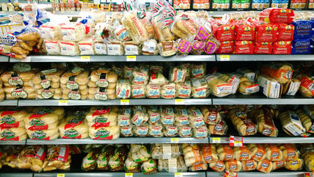 food shelf: Different types of bread on shelves in a grocery store