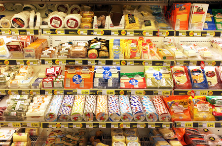 Different types of cheese on shelves in a grocery store