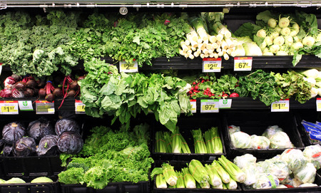Variety of green vegetables on shelves in a supermarket