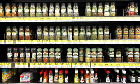 Various spices and seasoning powders on shelves in a supermarket