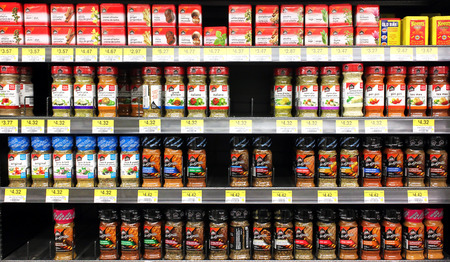 Variety of spices and seasoning powders on shelves in a supermarket