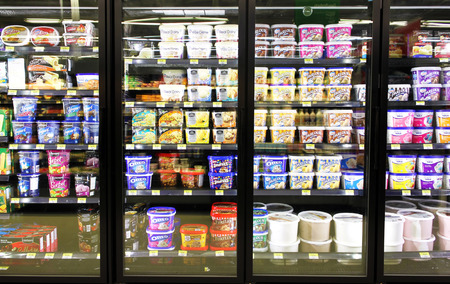 Different brands and flavors of ice cream on fridge shelves in a supermarket