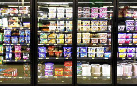 helado de chocolate: Las diferentes marcas y sabores de helados en los estantes del refrigerador en un supermercado