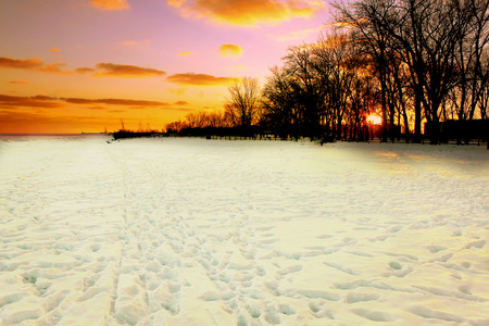 Sunset over a snow covered beach with footprints and trails in winter 스톡 콘텐츠