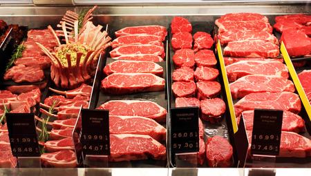 Selection of different cuts of fresh raw red meat in a supermarket photo