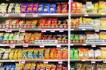 crisps: Potato chips and snacks on shelves in a supermarket