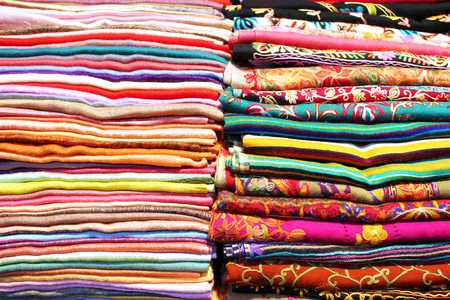woven: Stacks of folded colorful scarfs and fabrics Stock Photo