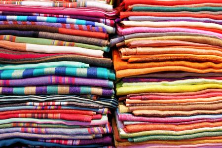 warm colors: Pilas de telas de colores cruzados y textil cerca de fondo