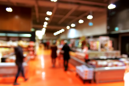 convenient store: Supermarket blur background with bokeh - shoppers at grocery store with defocused lights Stock Photo