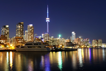 Toronto skyline at night over lake with colorful reflections