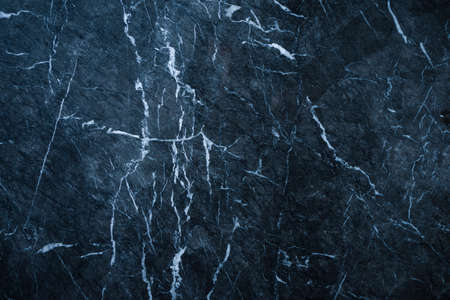 dark abstract marble texture background with blue tint and white veins